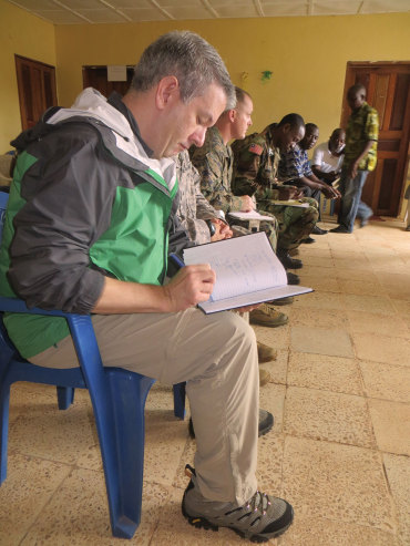 Patrick Flaherty '92 records observations during a meeting with health officials in Margibi County, Liberia to select a site for an Ebola Treatment Unit (ETU). The Armed Forces of Liberia will lead the construction of several ETUs in Liberia.