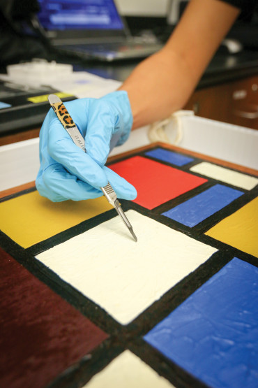Joo Yeon Roh '16 demonstrates how students remove samples using a mock artwork.