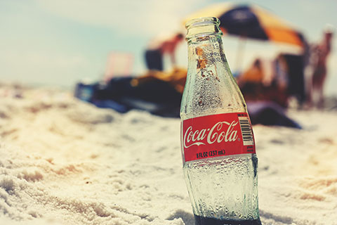 Coca-Cola bottle on sandy beach.